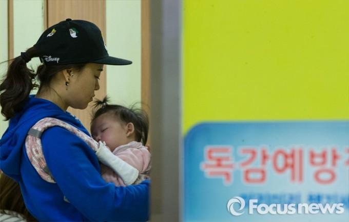 올해 1월 15일 인플루엔자 유행주의보가 발령된 바 있다. 이날 오전 서울 용산구 소화아동병원에서 한 엄마가 자녀와 진료 차례를 기다리는 모습. - 포커스뉴스 제공